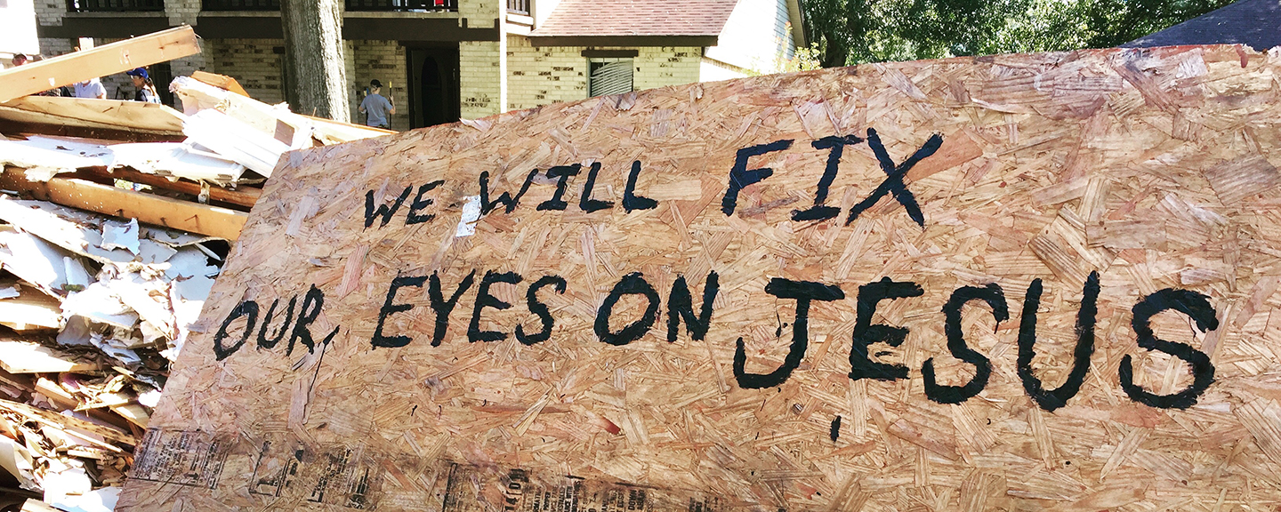 A large piece of plywood with a reference to Hebrews 12:2 sits atop a water-damaged sink in the front yard of a Houston family's home.