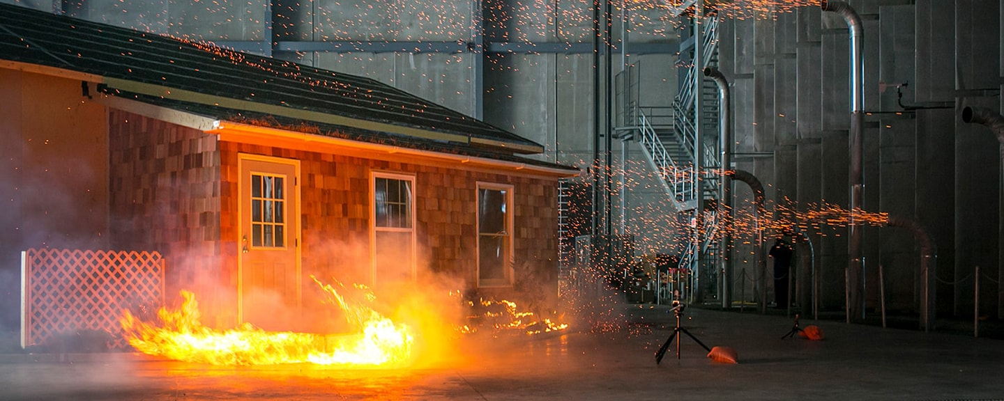 Ember generators blow burning wood embers onto a home inside the large test chamber at IBHS. <em>Courtesy of IBHS</em>